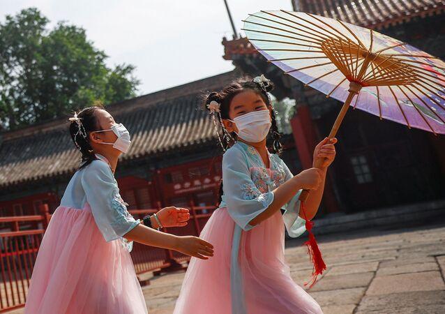 Crianças chinesas usam máscaras protetoras, na capital chinesa, Pequim, 22 de maio de 2020