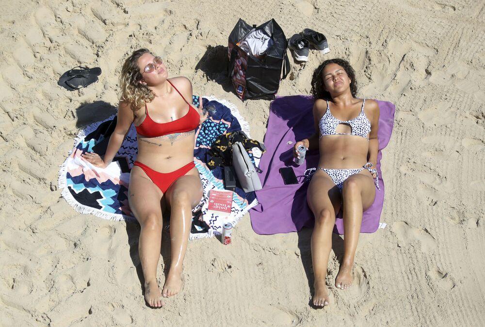Garotas tomam banho de sol em praia de Cullercoats, no Reino Unido, 20 de maio de 2020