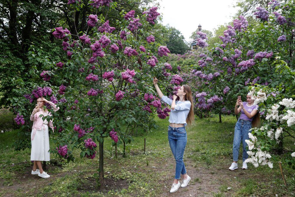 Mulheres tiram fotos em frente a flores em jardim botânico em Kiev, na Ucrânia, 18 de maio de 2020