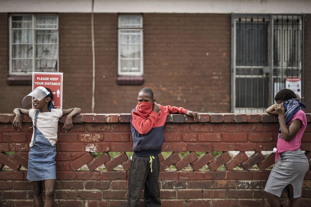 Crianças mantêm distanciamento seguro enquanto fazem fila para a distribuição de alimentos em Westbury, Joanesburgo, 19 de maio de 2020