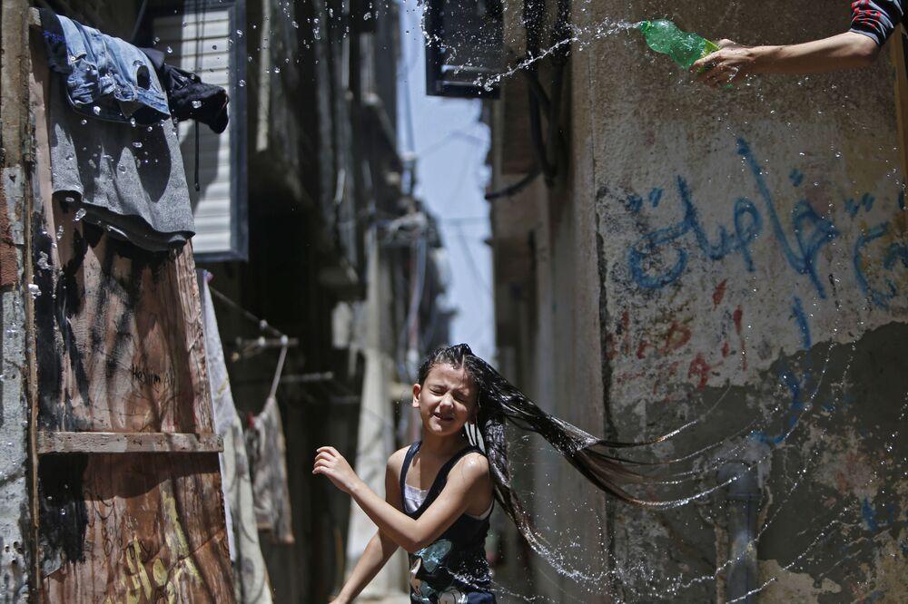 Menina palestina se refrescando durante uma onda de calor no centro da Faixa de Gaza em meio à pandemia da COVID-19, 19 de maio de 2020