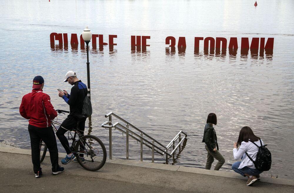 Residentes da cidade russa de Perm tiram foto perto de objeto de arte inundado após subida do nível da água no rio Kama