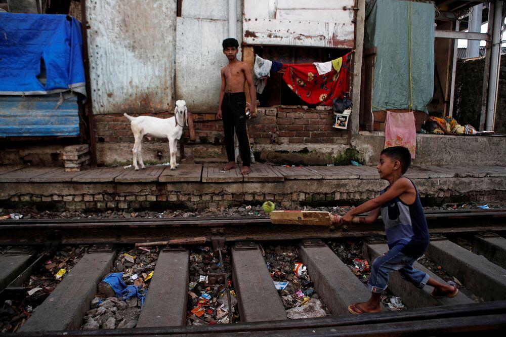Menino joga críquete em uma ferrovia abandonada, em Mumbai, Índia, 19 de maio de 2020