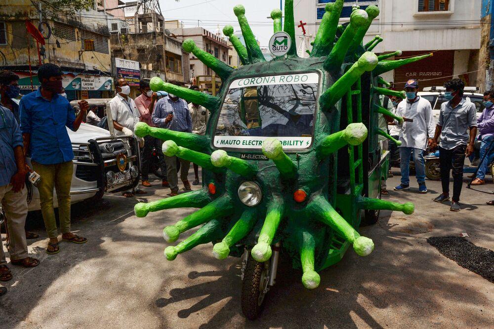 Trabalhador municipal dirige veículo com tema do coronavírus em rua de Chennai, na Índia, em 20 de maio de 2020