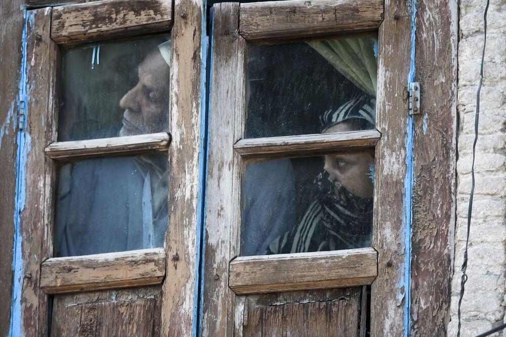 Moradores olham pela janela em área próxima ao local de um tiroteio entre supostos militantes e forças do governo em Srinagar, Índia, em 19 de maio de 2020