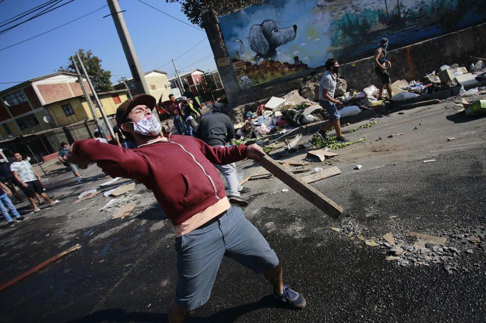 Manifestantes entram em confronto com a polícia de choque durante protesto contra o governo chileno em meio à pandemia, em Santiago, 18 de maio de 2020