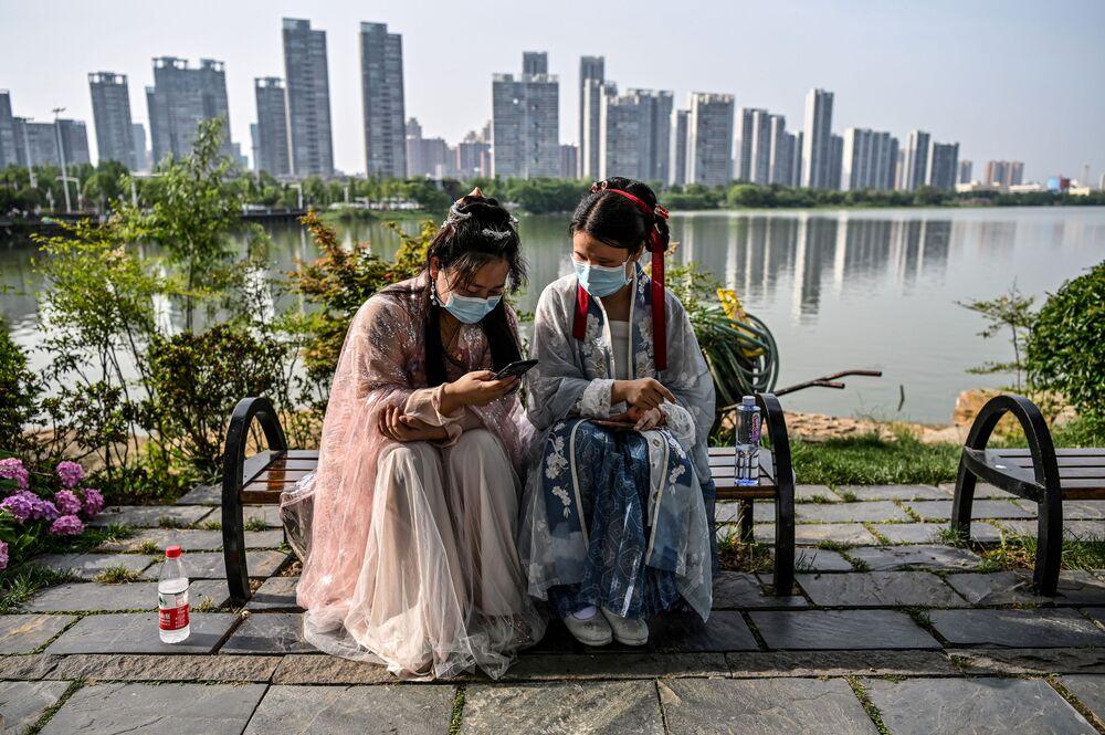 Mulheres vestindo máscaras e trajes tradicionais sentadas em banco em Wuhan, na província de Hubei, centro da China, em 17 de maio de 2020