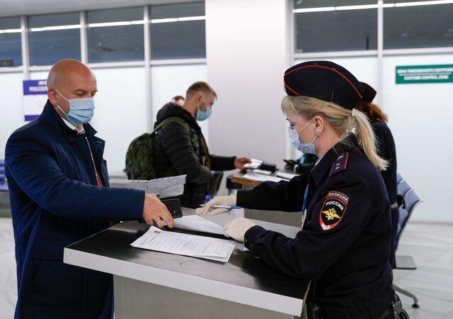 Passageiros na zona de controle aduaneiro do aeroporto de Khrabrovo, Kaliningrado, Rússia