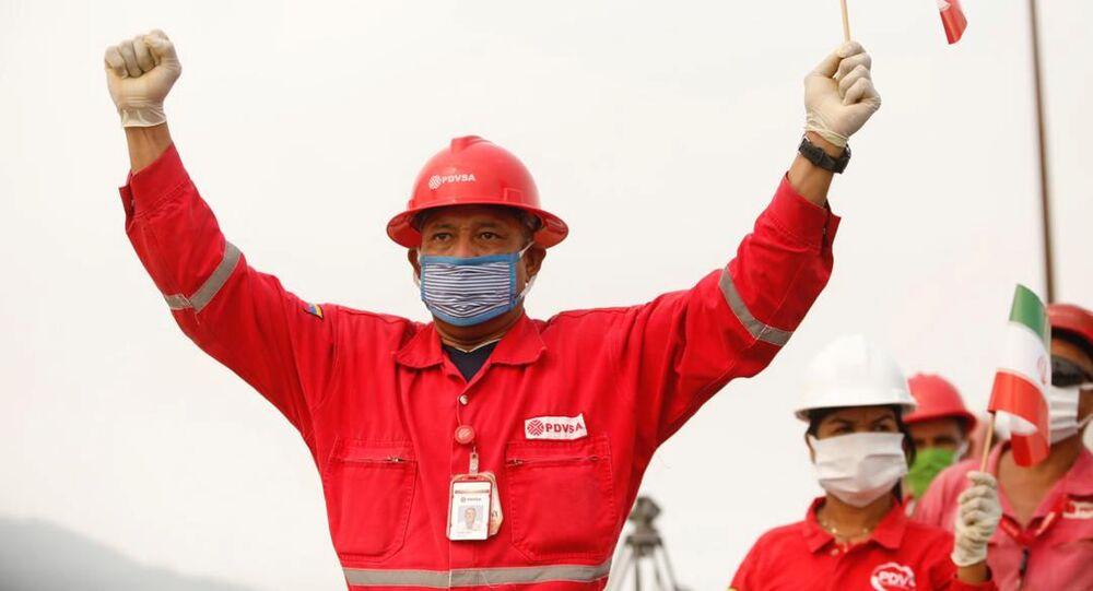 Funcionário da companhia de petróleo estatal venezuelana, PDVSA, com bandeira iraniana, após a chegada de petroleiro enviado por Teerã a Caracas, 25 de maio de 2020