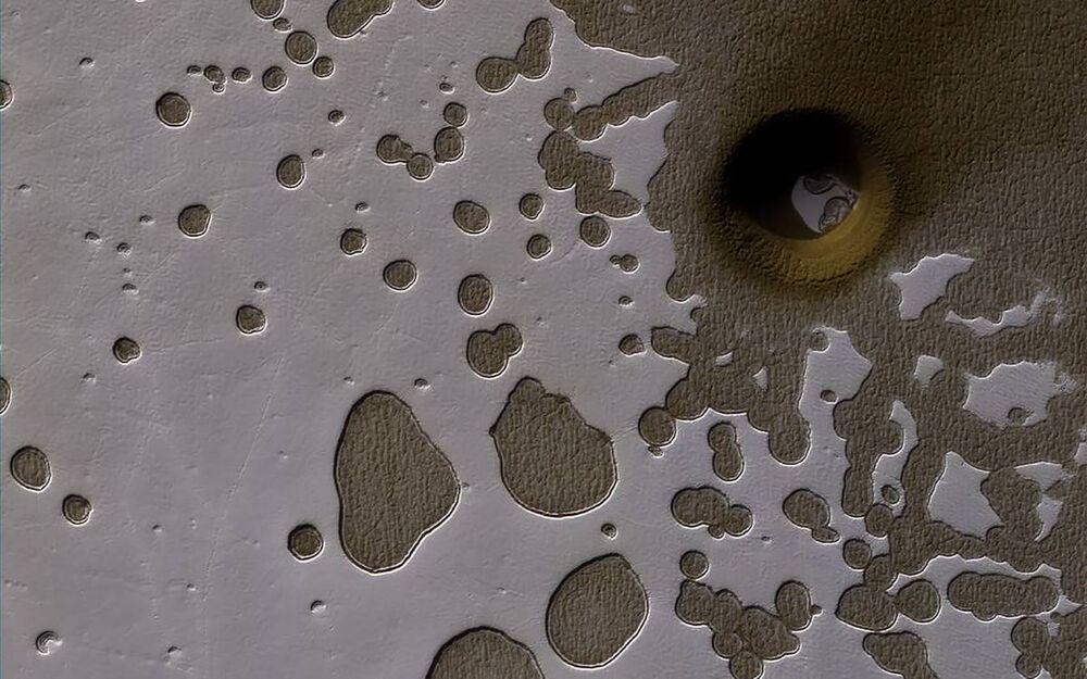 Pequenas covas em uma camada residual de gelo de dióxido de carbono, também conhecido como terreno de queijo suíço, na superfície marciana