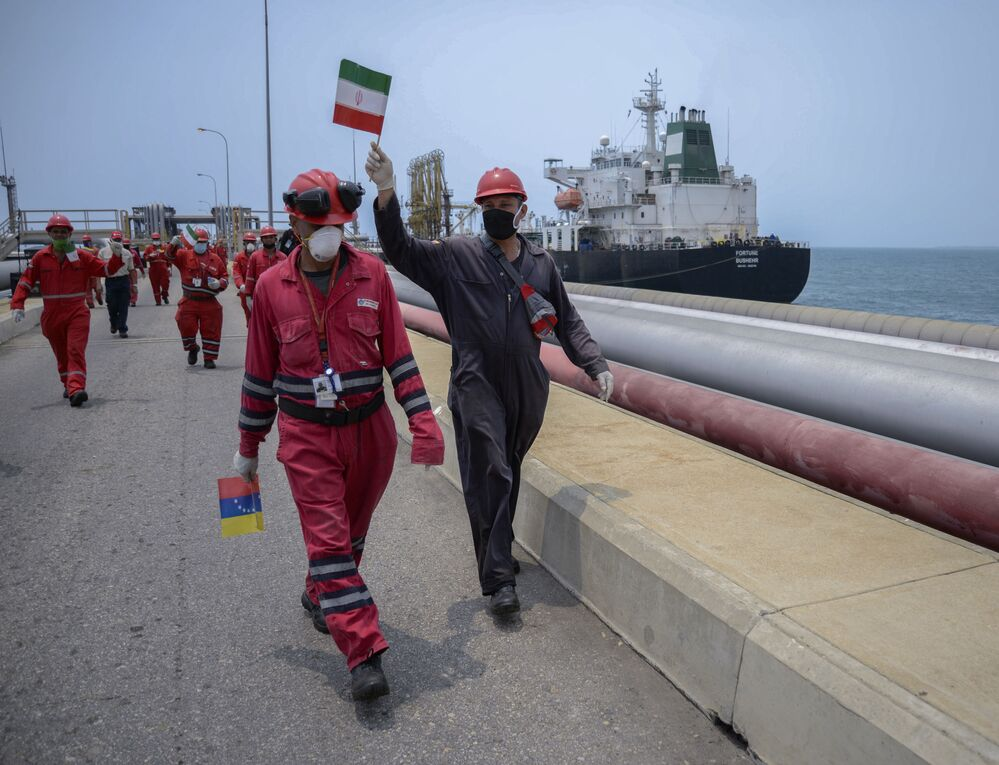 Funcionários venezuelanos com bandeiras do Irã comemoram chegada do petroleiro Fortune