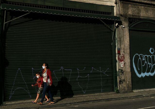Pedestres passam em frente a um comércio fechado durante a pandemia no Rio de Janeiro