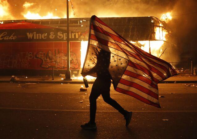 Manifestante carrega a bandeira dos EUA virada ao contrário, durante protestos em Minneapolis, 28 de maio de 2020