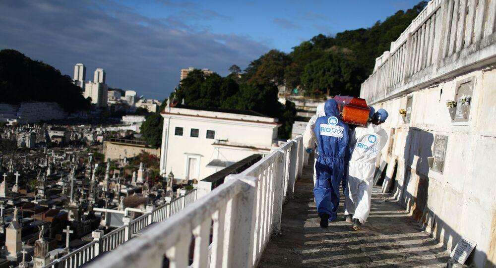 Funcionários do cemitério de São João Batista carregam caixão de vítima de COVID-19, no Rio de Janeiro, em 28 de maio de 2020