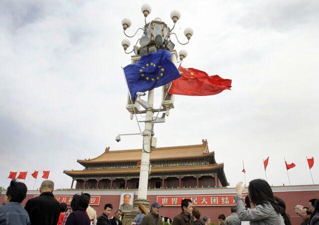 Visitantes caminham sob bandeiras da União Europeia e da China em frente à Porta de Tiananmen em Pequim, China