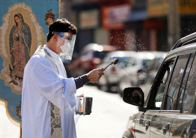 Padre católico dá a bênção a fiéis no Dia das Mães, na cidade de Curitiba, 10 de maio de 2020