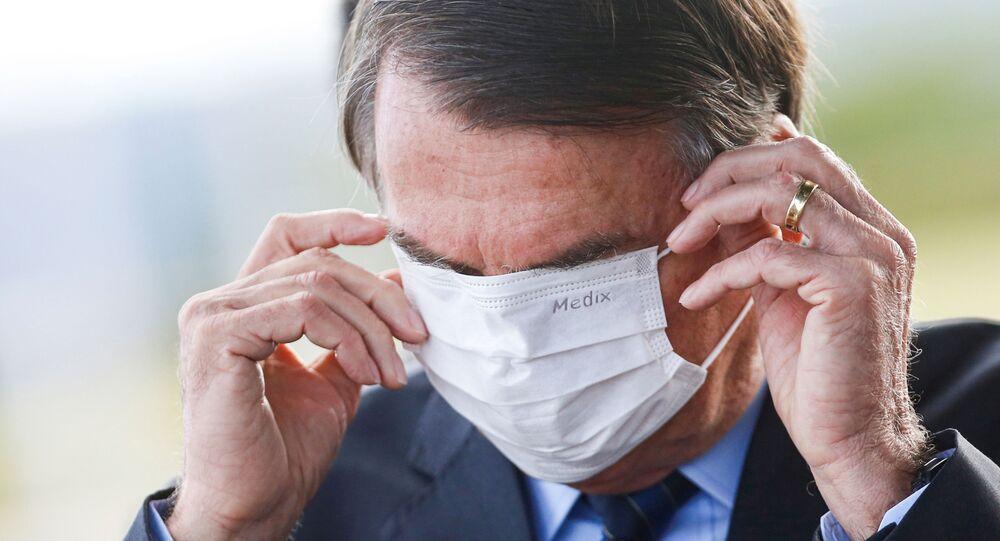 Presidente Jair Bolsonaro ajusta a sua máscara na saída do Palácio da Alvorada, em Brasília (DF)