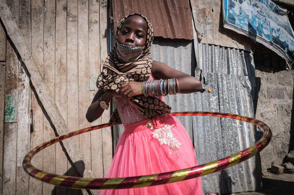 Menina órfã dança com bambolê durante ação de distribuição de comida e brinquedos para crianças órfãs em comemoração do feriado islâmico Eid al-Fitr, no Quênia