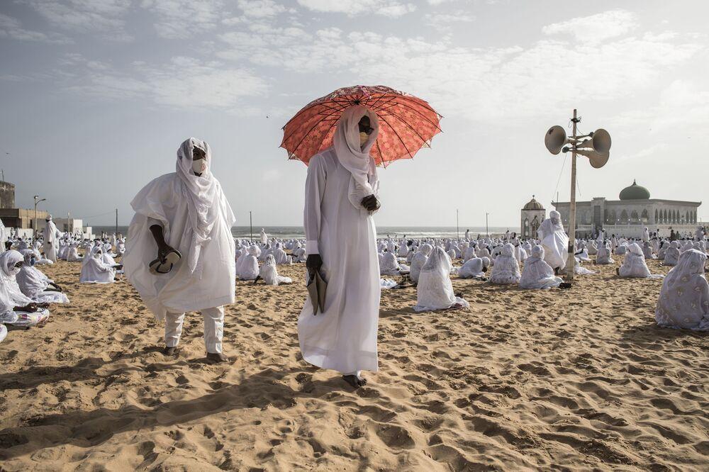 Seguidores da comunidade muçulmana Layene saem da praia em frente da mesquita Yoff Layene, no Senegal