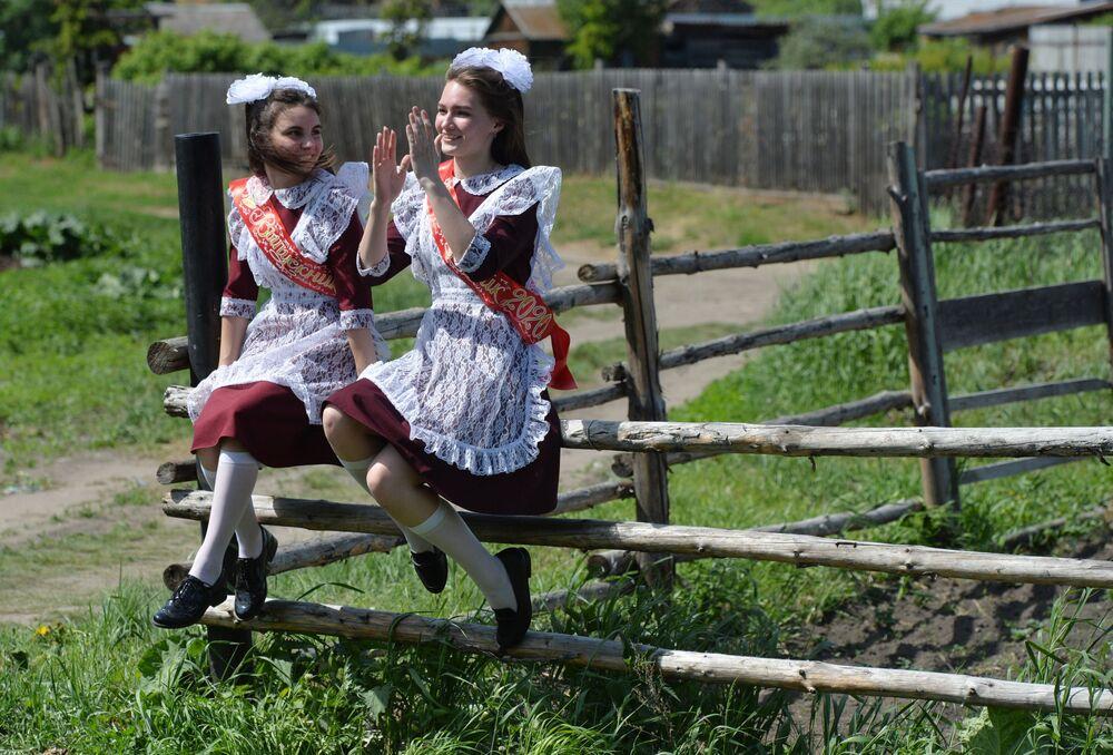 Meninas no dia da celebração de formatura escolar perto de sua escola no vilarejo russo de Miasskoe, na região de Chelyabinsk