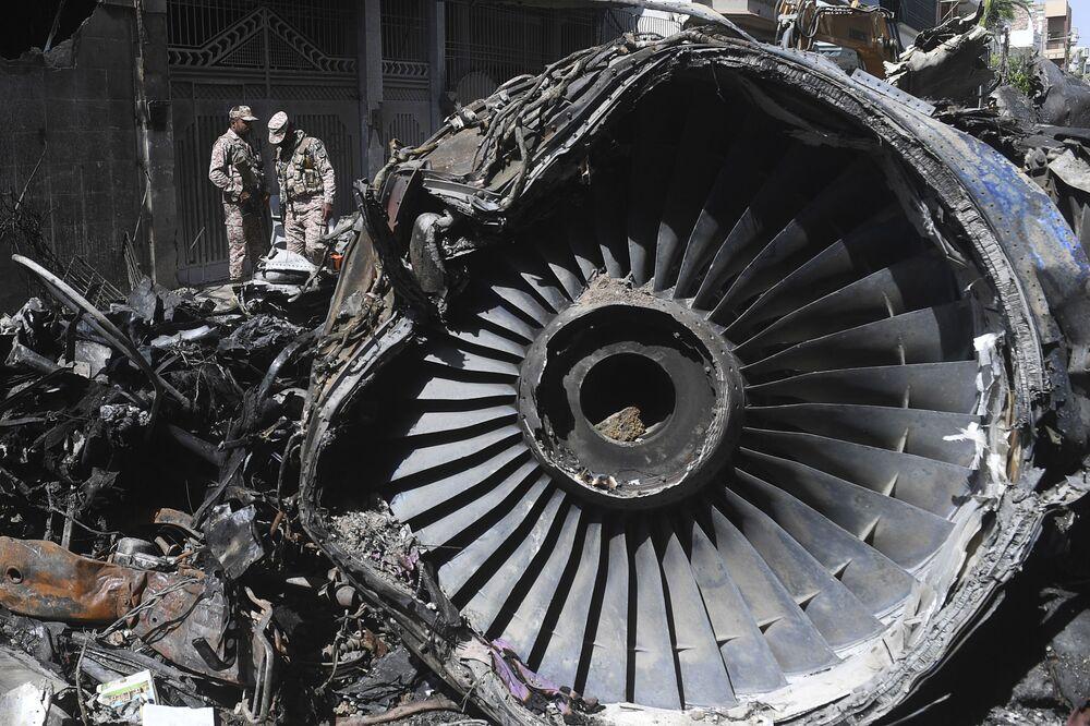 Agentes de segurança ao lado de destroços de aeronave Airbus 320 das Linhas Aéreas Paquistanesas que caiu em Carachi