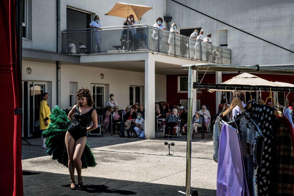 Atores da companhia teatral L' Espace des Arts durante show para moradores do asilo de idosos Bois de Menuse, em Chalon-sur-Saone, na França, durante a pandemia do coronavírus