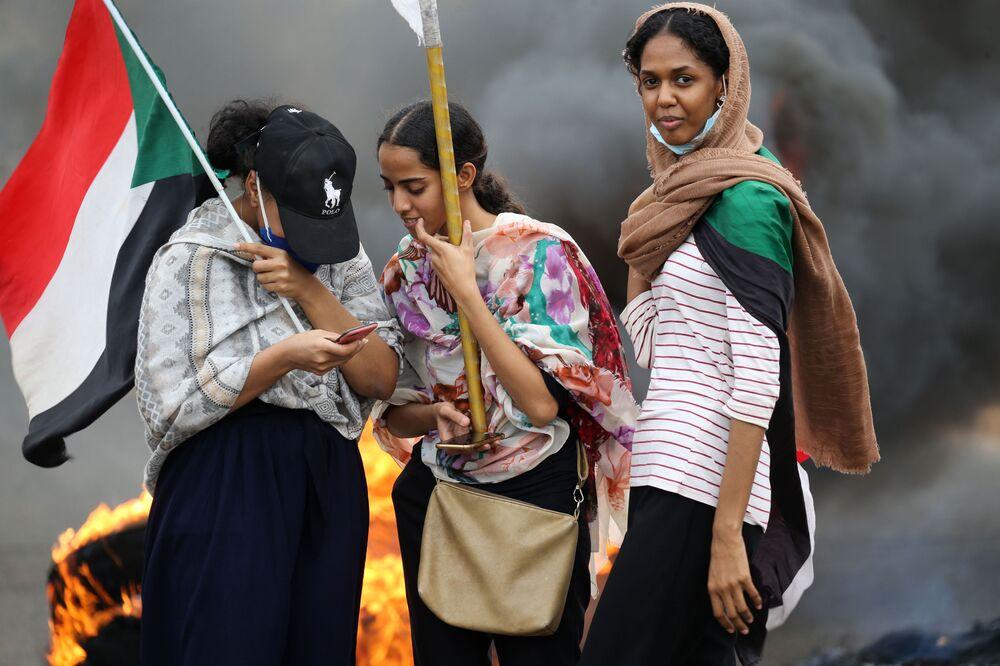 Mulheres levantam bandeiras durante ato em Cartum, no Sudão