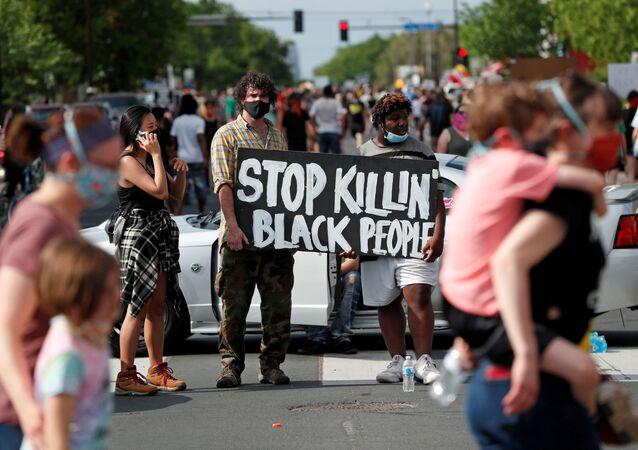 Americanos com máscaras nas ruas de Minneapolis protestam contra a morte de um cidadão negro, George Floyd, pela polícia da cidade