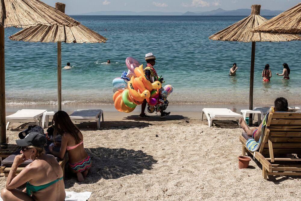 Banhistas descansam e homem vende boias na praia de Alimos nos arredores de Atenas, na Grécia