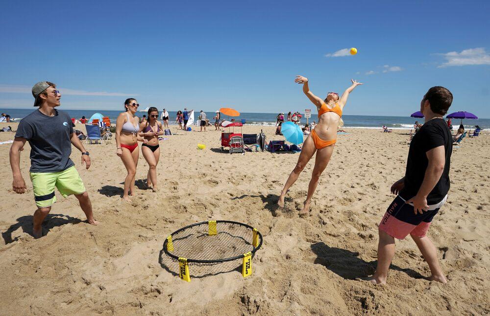 Jovens se divertem em praia de Ocean City, nos EUA, após redução das restrições da quarentena no país