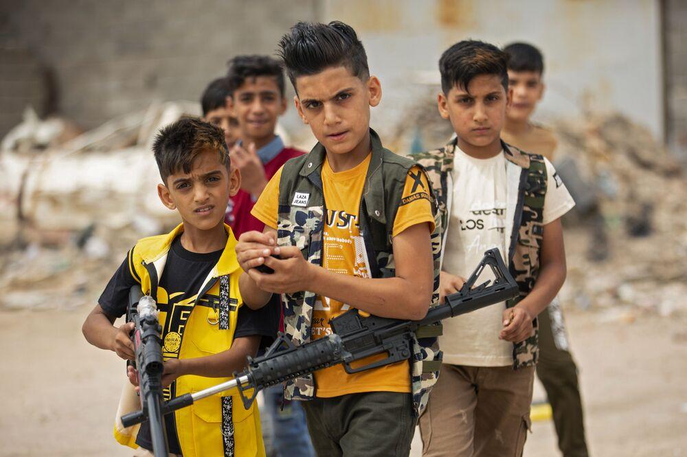 Crianças iraquianas brincam com armas de plástico durante o feriado islâmico de Eid al-Fitr, no fim do Ramadã, na cidade iraquiana de Basra