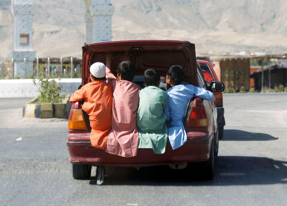 Crianças afegãs viajam em porta-malas de veículo durante o feriado islâmico de Eid al-Fitr na província afegã de Laghman