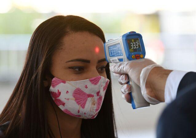 Moça tem temperatura verificada ao entrar em shopping em Brasília enquanto comércio em todo o Brasil começa a abrir com restrições