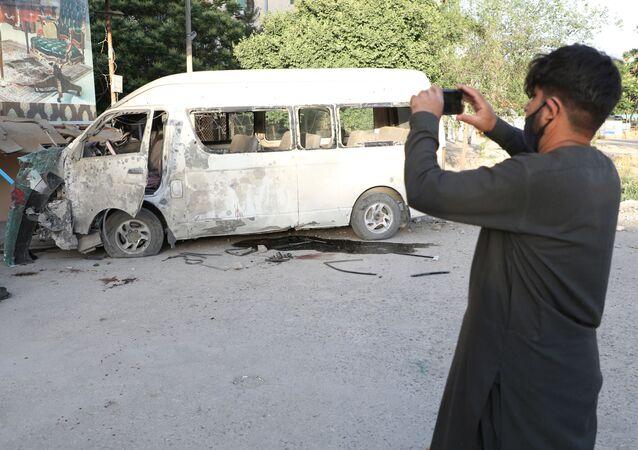 Um homem fotografa um veículo que foi atacado enquanto carregava funcionários de uma emissora em Cabul, no Afeganistão, em 30 de maio de 2020.