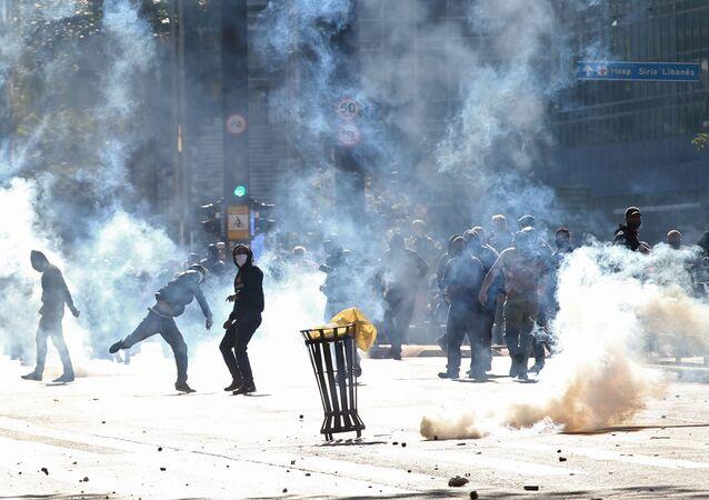 Manifestantes contra o presidente brasileiro Jair Bolsonaro em meio ao gás lacrimogênio lançado pela Polícia Militar, em São Paulo, em 31 de maio de 2020, durante manifestação pela democracia.