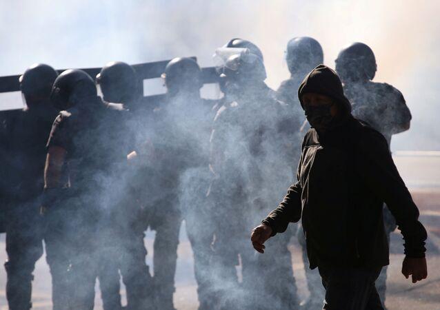 Um homem caminha em meio ao gás lacrimogênio enquanto policiais investem contra manifestação contra o presidente Jair Bolsonaro e a favor da democracia, em 31 de maio de 2020.