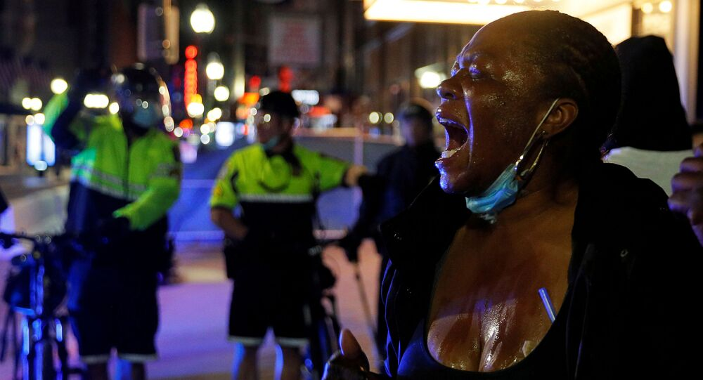 Manifestante reage após ser atingida por agente químico usado pela polícia para conter protestos em Boston, Massachusetts, EUA, 31 de maio de 2020