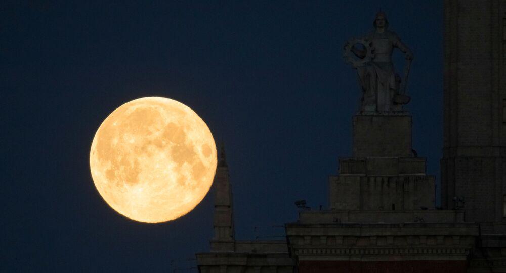 Lua cheia vista atrás da Universidade Estatal Lomonosov de Moscou, Rússia, 8 de maio de 2020