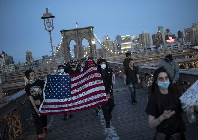 Manifestantes com a bandeira dos EUA protestam em Nova York contra o assassinato de George Floyd
