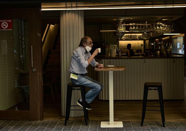 Homem toma café na cidade de Pamplona, na Espanha, em meio à pandemia da COVID-19.