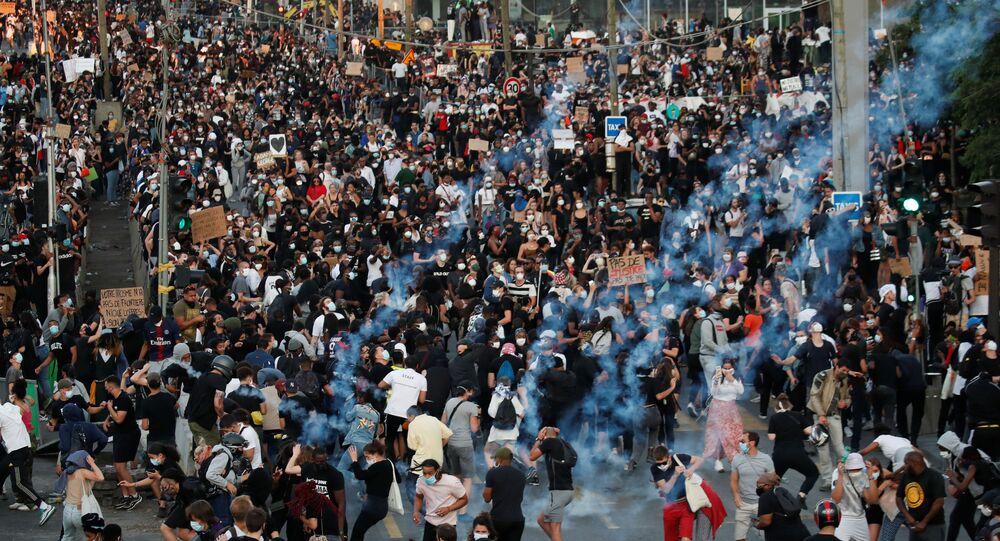 Em Paris, manifestantes fogem de gás lacrimogênio lançado pela polícia durante protesto antirracista, em 2 de junho de 2020, pedindo justiça pela morte de Adama Traore.