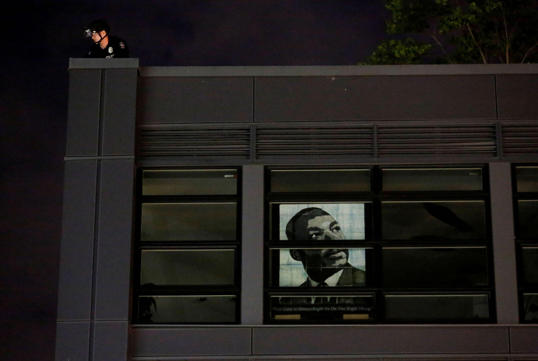 Policial observa manifestações, em cima de prédio no qual está exposta a imagem de Martin Luther King, Seattle, EUA, 4 de junho de 2020