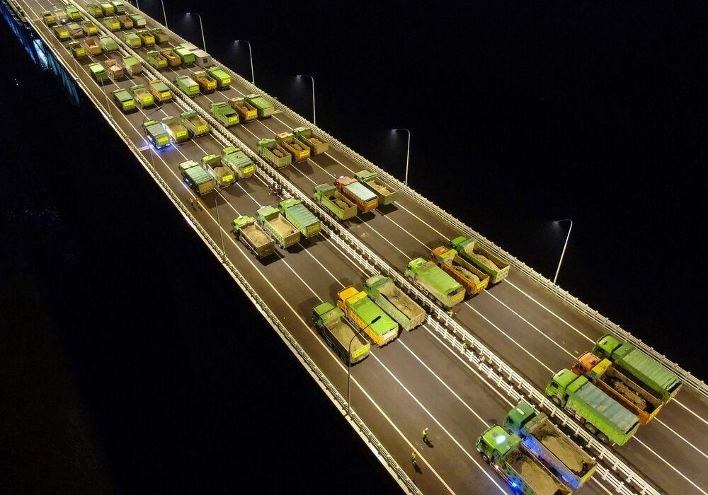 Vista área de caminhões dirigindo em teste de resistência da ponte Hutong, na China