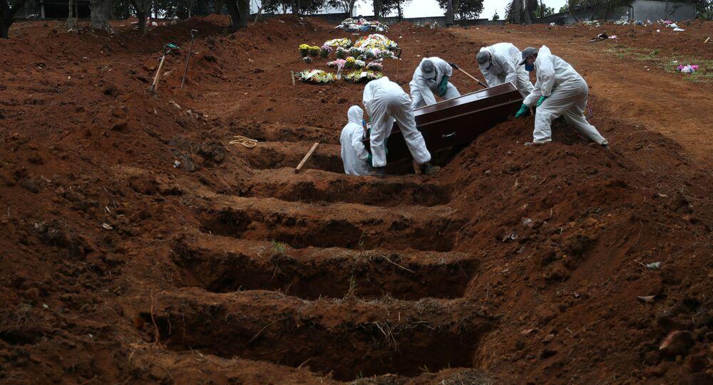 Funcionários de cemitério usam roupas protetoras durante funeral de homem de 48 anos, vítima da COVID-19, no Cemitério São Luiz, em São Paulo, 4 de junho de 2020