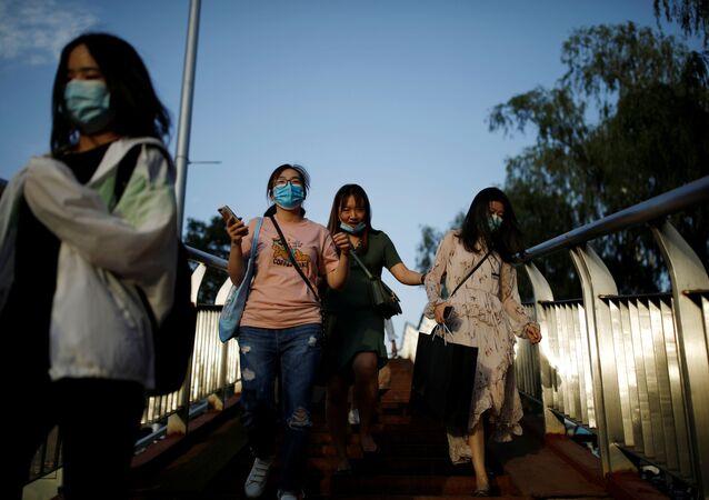 Pessoas usando máscaras faciais após o surto da doença do coronavírus (COVID-19) caminham por uma ponte para pedestres em Pequim, China, 4 de junho de 2020