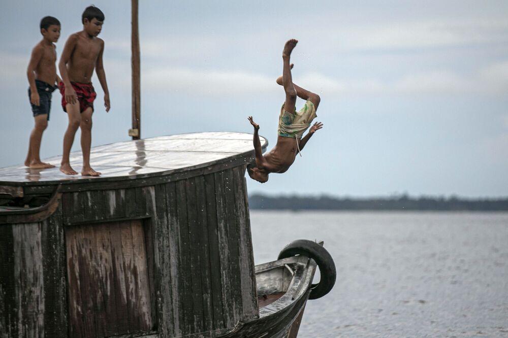 Criança pula na água na baía de Melgaço, no sudoeste da ilha de Marajó, no estado do Pará, Brasil, em 29 de maio de 2020