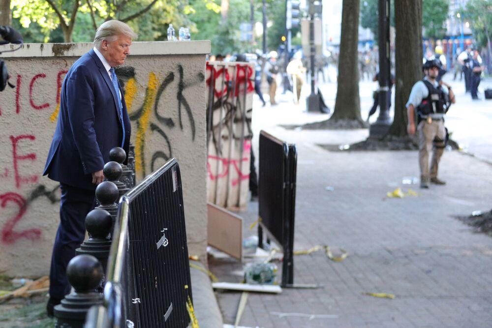 Presidente dos EUA, Donald Trump, passa por um prédio grafitado por manifestantes no parque Lafayette, em frente à Casa Branca, nos EUA