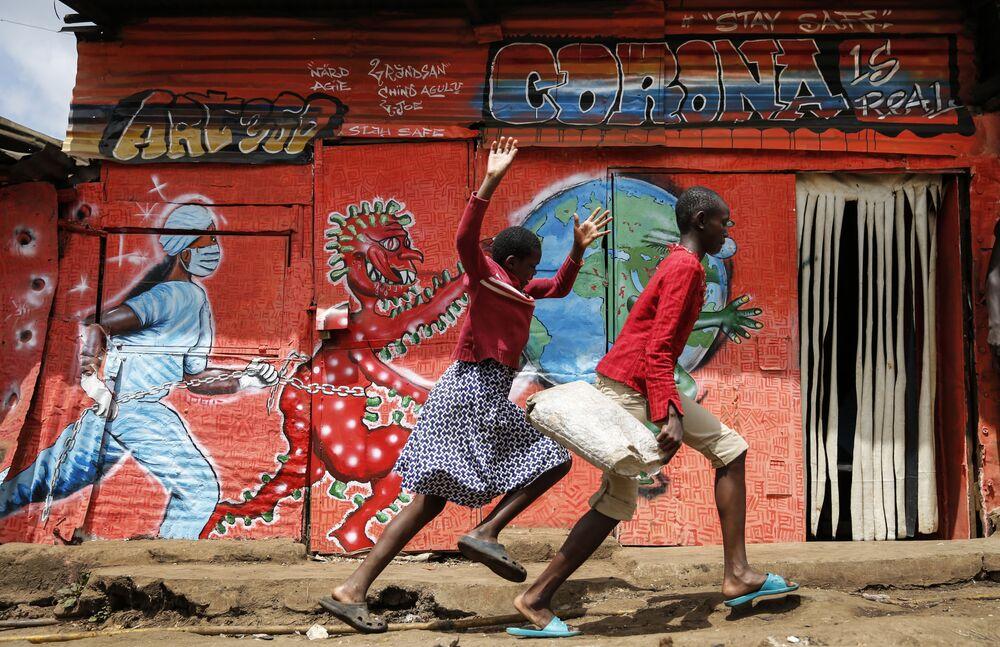 Crianças correm pela rua passando por mural informativo alertando sobre os perigos do novo coronavírus em favela de Nairóbi, no Quênia, 3 de junho de 2020