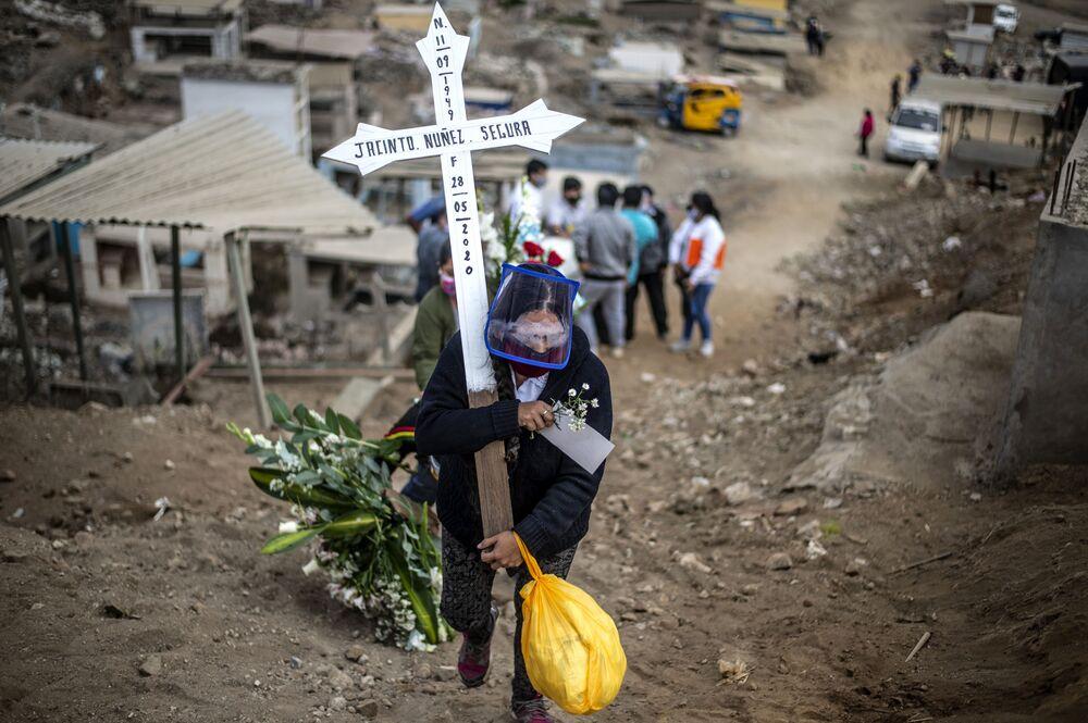 Parente de uma suposta vítima da COVID-19 carrega cruz durante o enterro no cemitério Nueva Esperanza, um dos maiores da América Latina, nos arredores do sul de Lima em 30 de maio de 2020