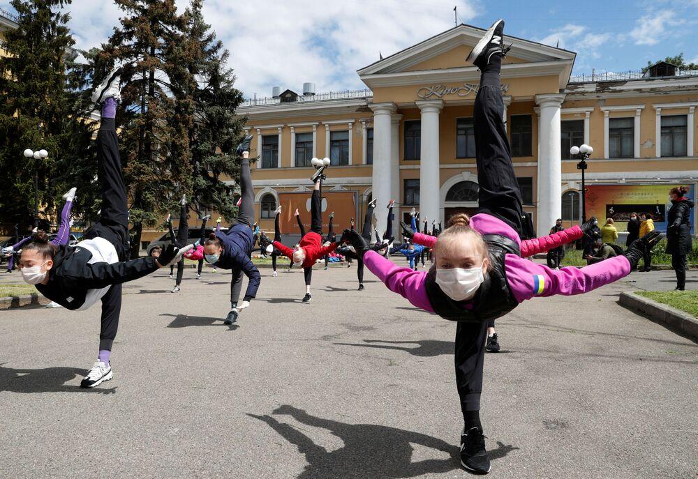 Alunos de escola de ginástica rítmica, usando máscaras e luvas, participam de uma sessão de treinamento ao ar livre em Kiev, Ucrânia